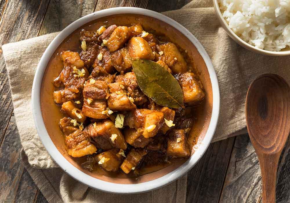 Philippinisches Adobo Gericht in einer Schale mit Löffel auf einem dekorierten Tisch mit Reis