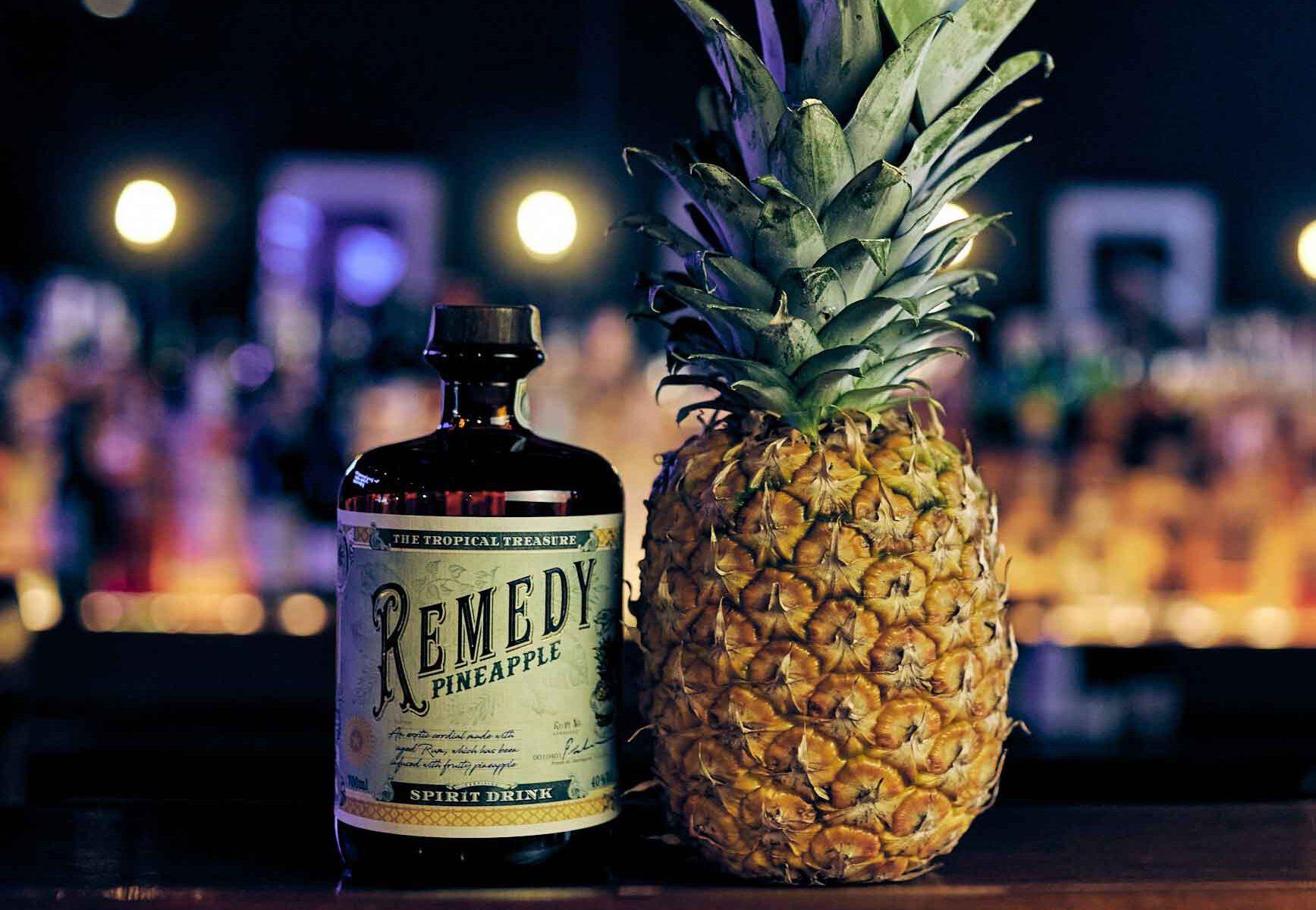 Remedy Pineapple Flasche mit einer tropischen Ananas daneben in einer Barumgebung